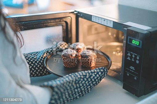 an asian chinese female putting cakes on a plate to microwave to heat up wearing kitchen glove