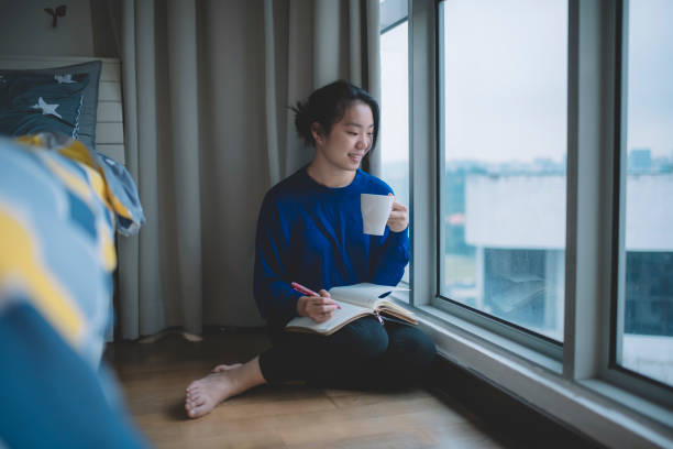 an asian chinese female student sitting beside the bed in bedroom with her coffee cup and writing on the note pad with toothy smile stock photo