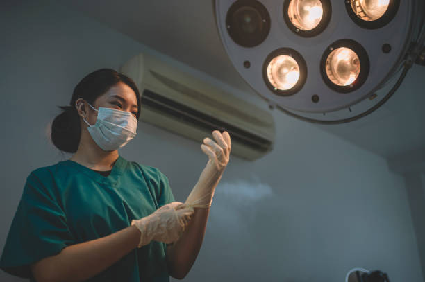 an asian chinese female surgeon getting ready and putting her surgical gloves on in the operating room illumined by surgical light stock photo