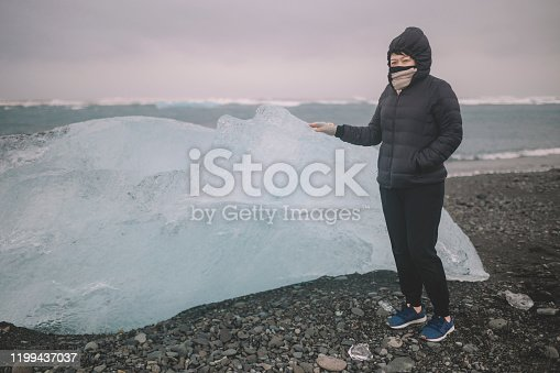 629376126istockphoto an asian chinese female traveler in front of iceberg glacier of iceland during overcast day with warm clothing hooded shirt looking away 1199437037