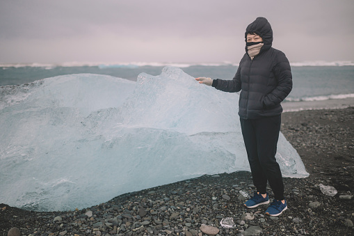 629376126 istock photo an asian chinese female traveler in front of iceberg glacier of iceland during overcast day with warm clothing hooded shirt looking away 1199437037