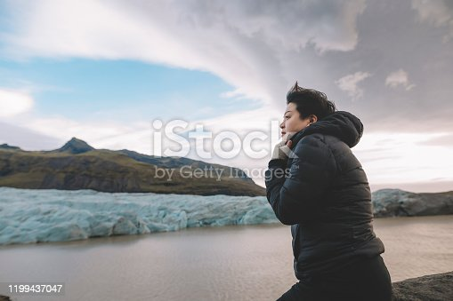 629376126istockphoto an asian chinese female traveler in front of iceberg glacier of iceland during overcast day with warm clothing hooded shirt looking away 1199437047