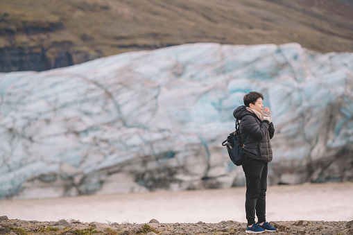 629376126 istock photo an asian chinese female traveler in front of iceberg glacier of iceland during overcast day with warm clothing hooded shirt looking away 1199437052