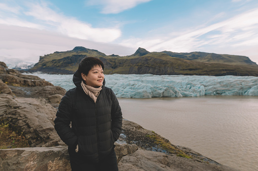 629376126 istock photo an asian chinese female traveler in front of iceberg glacier of iceland during overcast day with warm clothing hooded shirt 1199437059