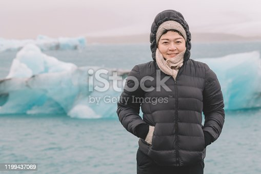 629376126istockphoto an asian chinese female traveler in front of iceberg glacier of iceland during overcast day with warm clothing hooded shirt looking at camera 1199437069