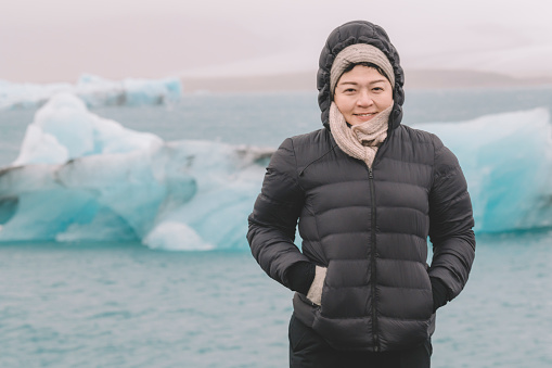 629376126 istock photo an asian chinese female traveler in front of iceberg glacier of iceland during overcast day with warm clothing hooded shirt looking at camera 1199437069