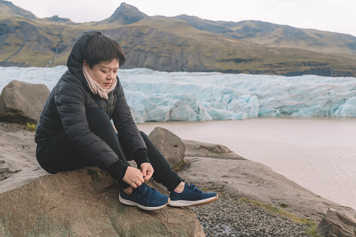 629376126 istock photo an asian chinese female traveler in front of iceberg glacier of iceland during overcast day with warm clothing hooded shirt tying her shoes 1199437081