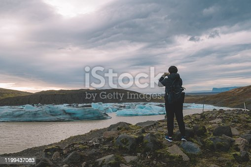 629376126istockphoto an asian chinese female traveler in front of iceberg glacier of iceland during overcast day with warm clothing hooded shirt taking photograph using her phone 1199437083