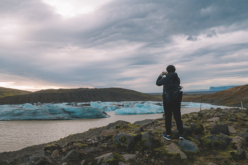 629376126 istock photo an asian chinese female traveler in front of iceberg glacier of iceland during overcast day with warm clothing hooded shirt taking photograph using her phone 1199437083