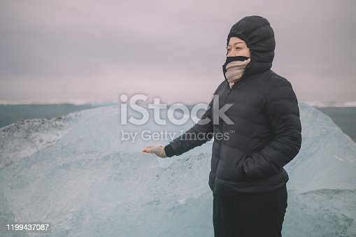 629376126istockphoto an asian chinese female traveler in front of iceberg glacier of iceland during overcast day with warm clothing hooded shirt looking away 1199437087
