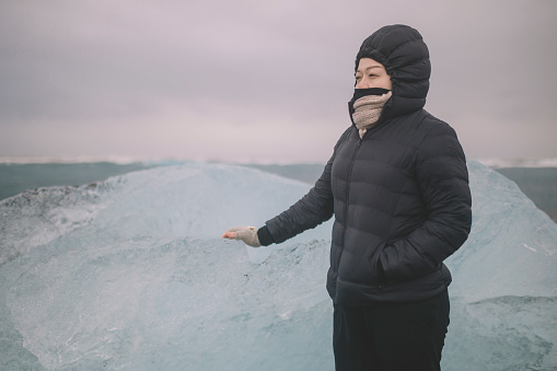 629376126 istock photo an asian chinese female traveler in front of iceberg glacier of iceland during overcast day with warm clothing hooded shirt looking away 1199437087