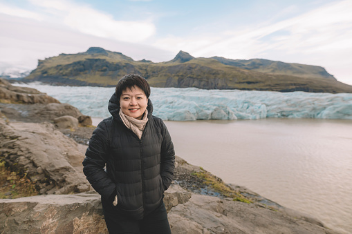 629376126 istock photo an asian chinese female traveler in front of iceberg glacier of iceland during overcast day with warm clothing hooded shirt looking at camera 1199437100