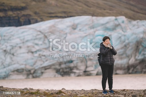 629376126istockphoto an asian chinese female traveler in front of iceberg glacier of iceland during overcast day with warm clothing hooded shirt looking away 1199437118