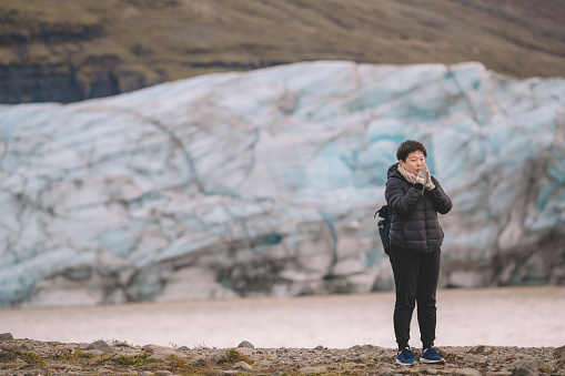 629376126 istock photo an asian chinese female traveler in front of iceberg glacier of iceland during overcast day with warm clothing hooded shirt looking away 1199437118