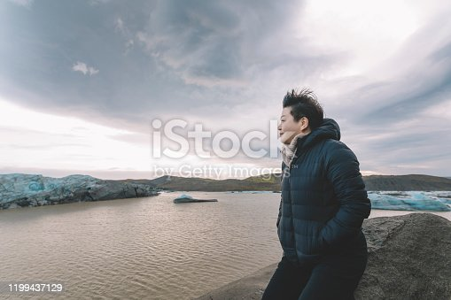 629376126istockphoto an asian chinese female traveler in front of iceberg glacier of iceland during overcast day with warm clothing hooded shirt looking away 1199437129