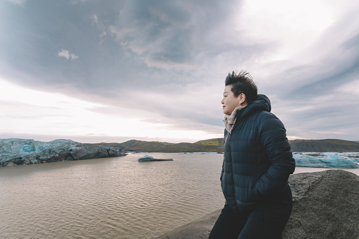 629376126 istock photo an asian chinese female traveler in front of iceberg glacier of iceland during overcast day with warm clothing hooded shirt looking away 1199437129