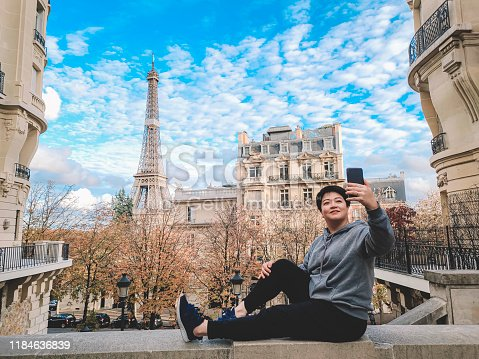 an asian chinese female traveller taking selfie photo in front of famous place eiffel tower during day time