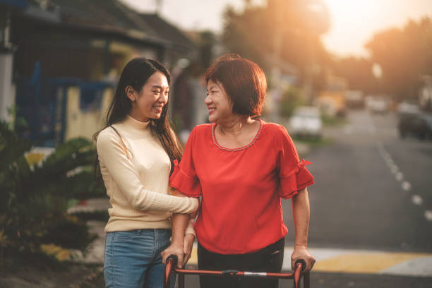 an asian chinese female walking with her walking aid recovering and helped by her daughter an asian chinese female walking with her walking aid recovering and helped by her daughter old mother son asian stock pictures, royalty-free photos & images