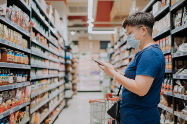 an asian chinese female wearing a mask going out shopping in supermarket looking at phone checking list stock photo