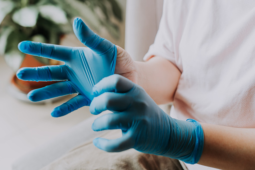 an asian chinese female wearing her latex surgical gloves at home before the cleaning process
