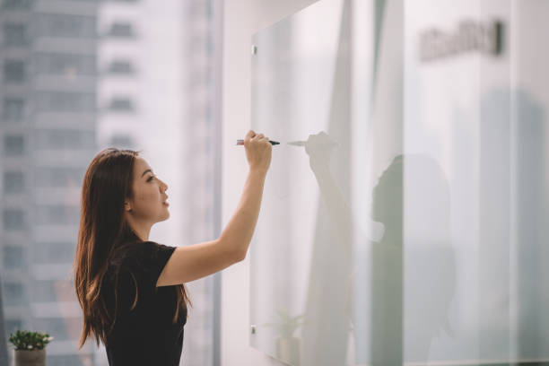 an asian chinese female writing on white board with her marker pen during conference meeting in office conference room stock photo
