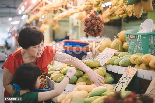an asian chinese grandmother selecting mango from the fruit stall from market with her granddaughter during weekend