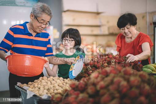 an asian chinese grandparents are selecting lanzone and rambutan at the fruit stall with their grandchild