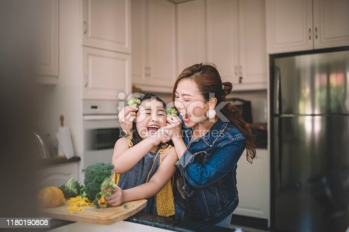 An Asian Chinese housewife having bonding time with her daughter in kitchen preparing food