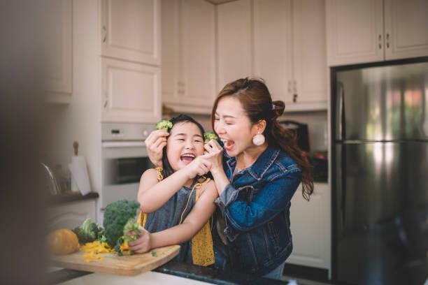 一位亞裔中國家庭主婦與女兒在廚房準備食物 - 亞洲 個照片及圖片檔