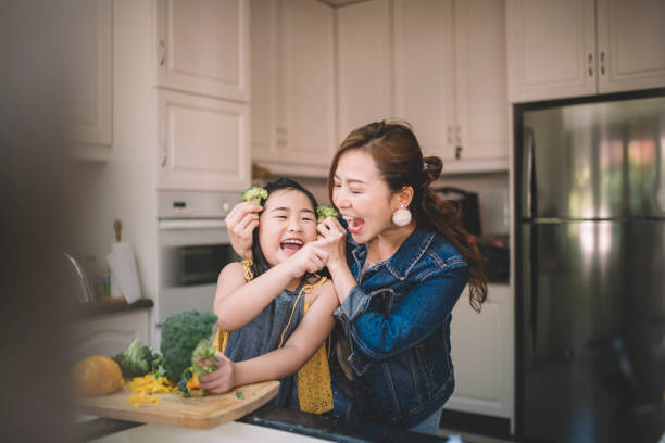 an asian chinese housewife having bonding time with her daughter in kitchen preparing food - ásia imagens e fotografias de stock