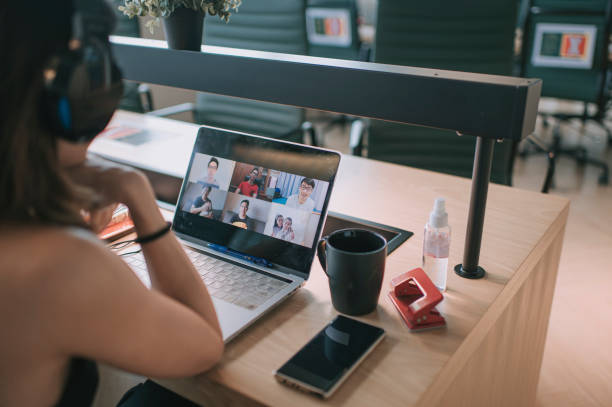 an asian chinese long hair woman having video conference call with her business partners in coworking office - new normal foto e immagini stock