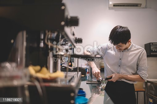 An asian chinese male barista cafe owner making expresso with a tamper