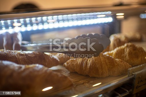 an asian chinese male cafe shop owner retrieving a croissant from the fridge