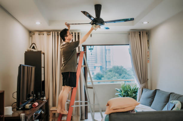an asian chinese male cleaning ceiling fan at home an asian chinese male cleaning ceiling fan at home ceiling fan stock pictures, royalty-free photos & images