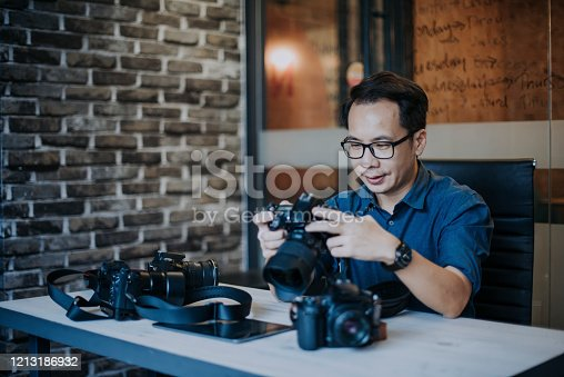 an asian chinese male photographer looking at his dslr camera collection in his office