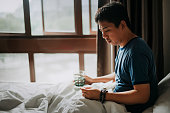 an Asian Chinese male sick illness at home and checking his body temperature using a thermometer and taking medicine with water on a bed