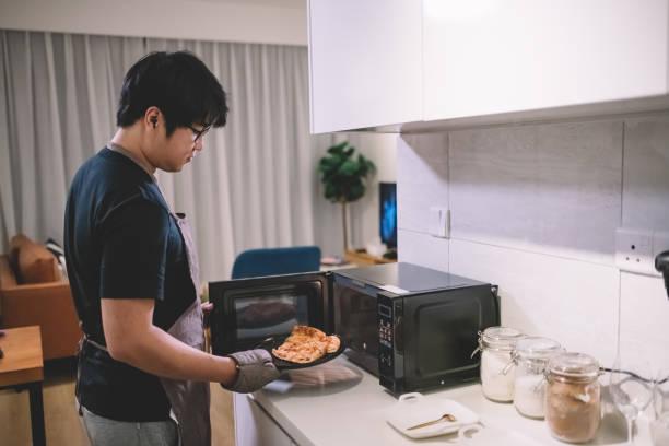einen asiatischen chinesischen mann nehmen eine pizza aus der mikrowelle in der küche mit handschuh - hausmannskost stock-fotos und bilder