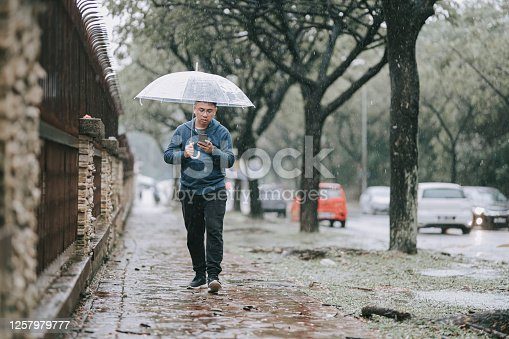 an asian chinese male walking in the rain on the street