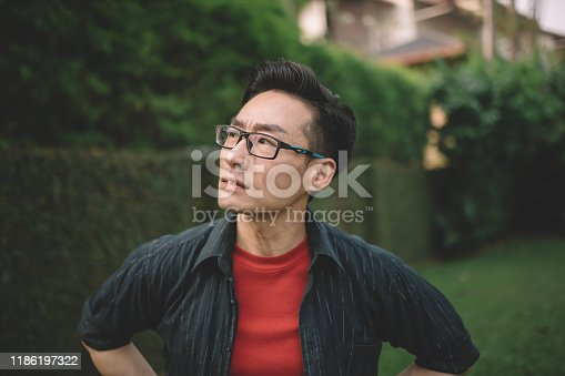 an asian chinese male with eyeglasses showing facial expression outdoor