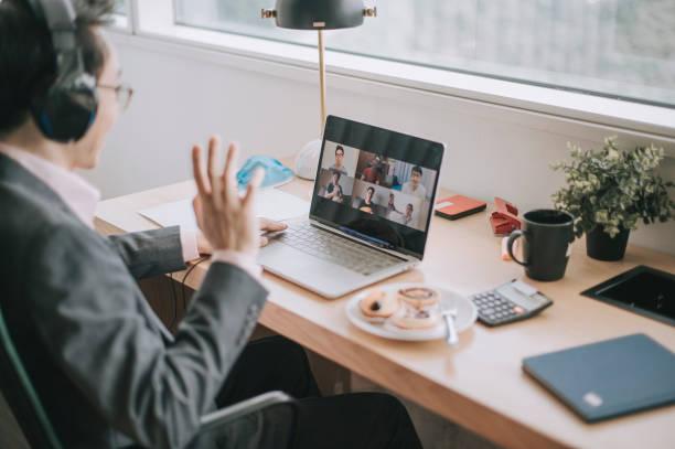un homme d'affaires chinois asiatique moyen adulte ayant la vidéoconférence avec son collègue et les partenaires d'affaires dans le bureau utilisant le casque et l'ordinateur portatif - business malaysia photos et images de collection