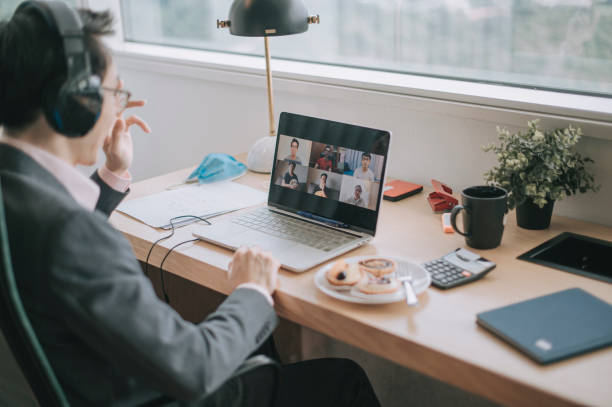 an asian chinese mid adult businessman having video conference with his colleague and business partners  in the office using headset and laptop - new normal foto e immagini stock