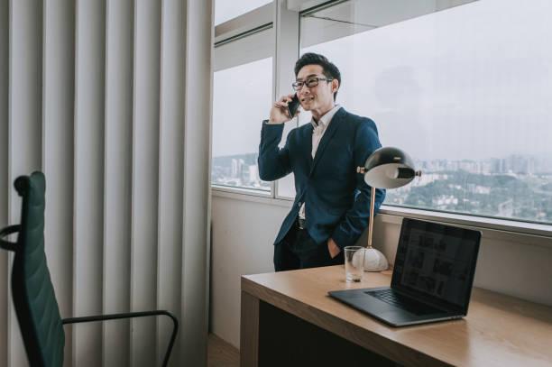 彼の携帯電話を聞いてオフィスで働くアジアの中国の中年のハンサムなホワイトカラー労働者 - business malaysia ストックフォトと画像