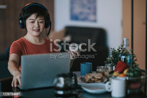 an asian chinese mid adult having breakfast in dining room while using laptop to reply emails in the morning
