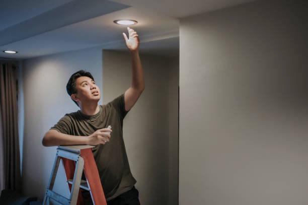 eine asiatische chinesische mittlere erwachsene männliche wechselnde glühbirne im wohnzimmer, wohnung zu hause - glühbirne auswechseln stock-fotos und bilder