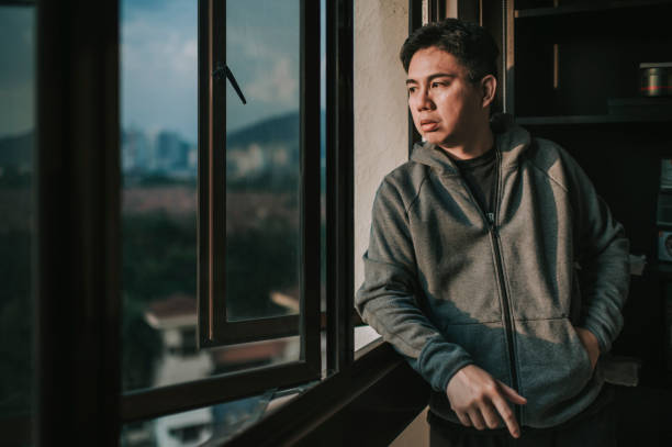 an asian chinese mid adult man looking outside of window from his home during sunset with serious facial expression with hooded shirt stock photo