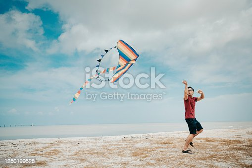 an asian chinese mid adult man playing and flying kite at beach