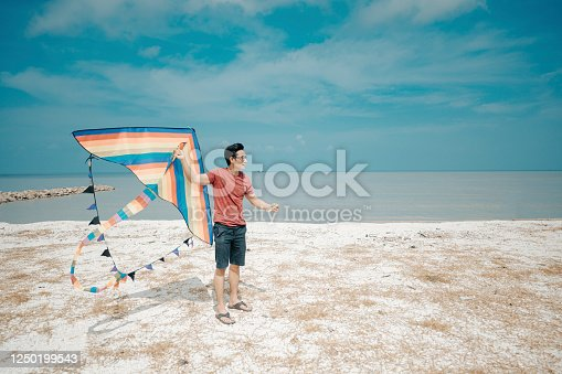 453383283 istock photo an asian chinese mid adult man playing and flying kite at beach 1250199543