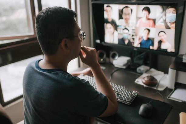 アジアの中国人中期成人男性が、自宅のコンピュータモニター画面からカメラディスカッションを見てオンラインで友人やビジネスパートナーと話し合い、コミュニケーションを取る - business malaysia ストックフォトと画像