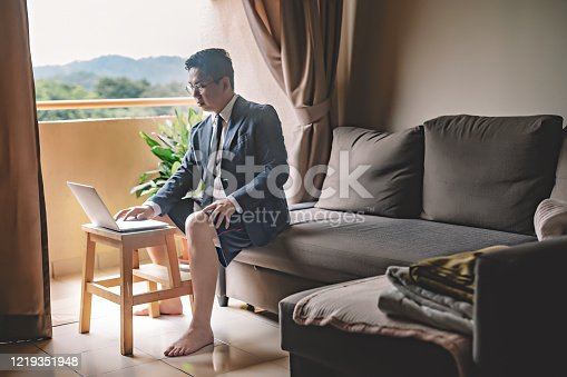 an asian chinese mid adult man with tie and suit and short pant sitting on sofa using laptop in his living room for video conference with his business partner and colleague virtual business meeting