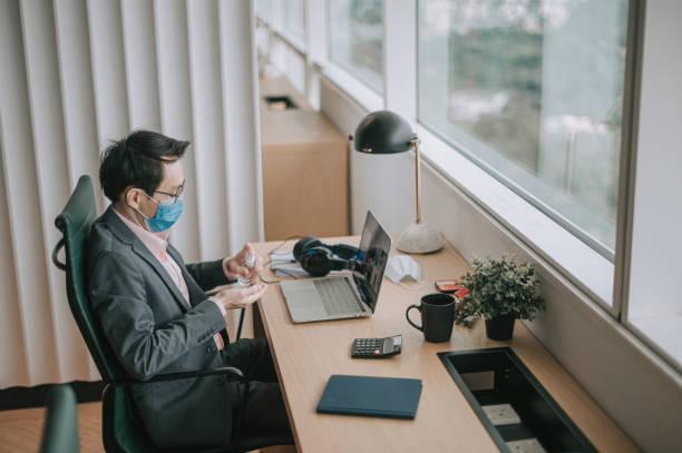 un homme chinois asiatique de col blanc adulte moyen nettoyant sa main avec le désinfectant de main devant son poste de travail - prise électrique à trois fiches photos et images de collection